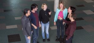 Mitarbeiter des Themenclusters stehen im Halbkreis auf einem türkis, weiß, schwarz und grau gefliestem Boden einer Halle und diskutieren. Das Bild ist schäg von Oben aufgezeichnet, so dass im Hintergrund der Personen nur der Boden zu sehen ist.